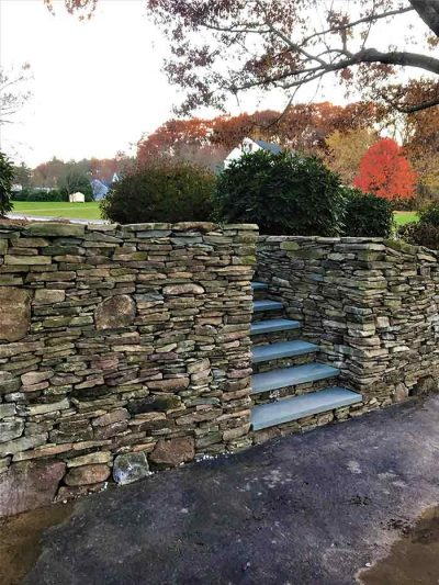 Veneer stone wall and steps with bluestone treads in front yard.