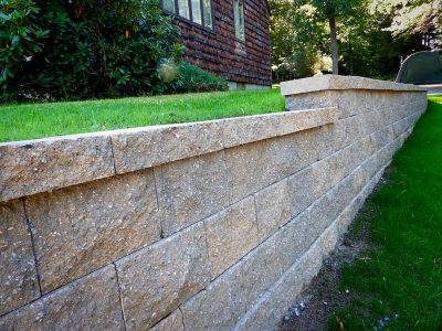 Modular block stone wall on side of house.