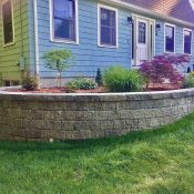 front yard planting bed modular block retaining wall with plants and mulch