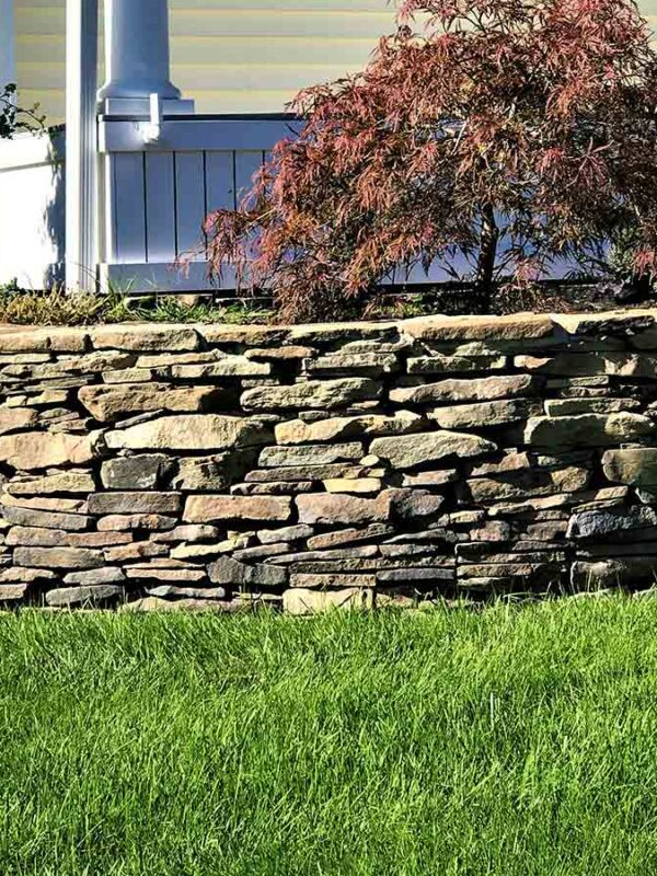 front yard natural fieldstone retaining wall with planting beds