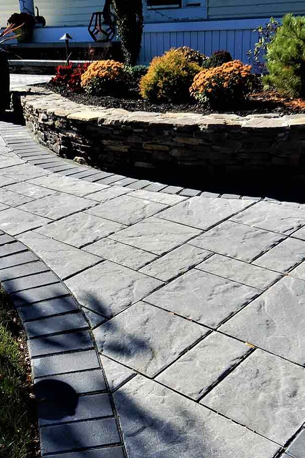 front home paver walkway entrance and fieldstone retaining wall around garden bed