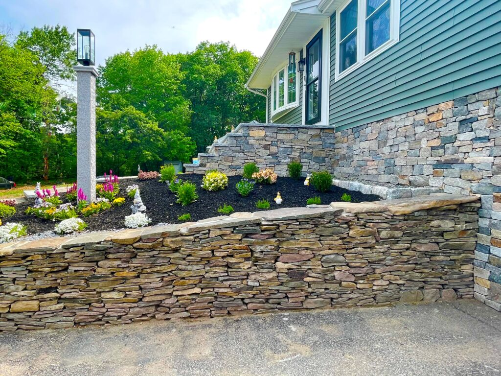 veneer home foundation with retaining wall and granite lamp post