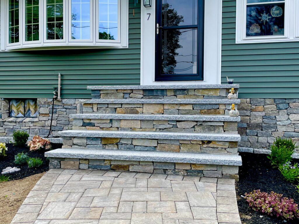 front entryway custom veneer stone steps with granite treads and paver walkway