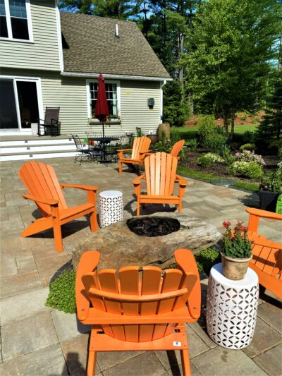 back yard paver patio landscape with stone fire pit and Adirondack chairs