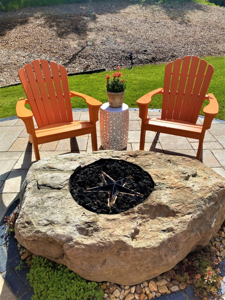 natural stone fire pit sitting area in back yard with chairs