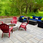 outdoor paver patio with circular fire pit and sitting wall